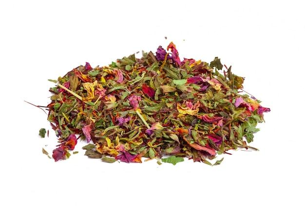 Zielona herbata z suchymi kwiatami na bielu. ścieśniać