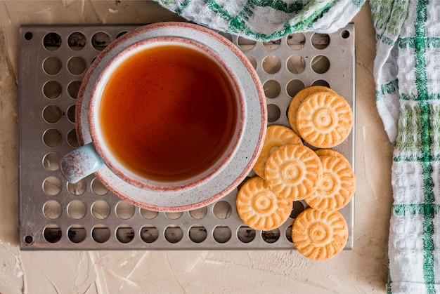 Zielona herbata ziołowa jest podawana na metalowej, zabytkowej tacy retro z domowymi ciastami