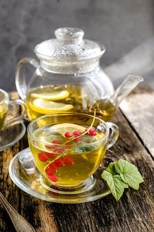 Zielona herbata ziołowa z jagodami w szklanej filiżance na drewnianym stole