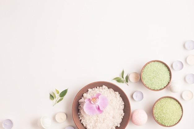 Zielona i biała ziołowa sól morska z wiele małych świeczki nad białym tłem