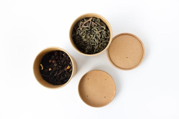 Zielona i czarna herbata w okrągłym opakowaniu kartonowym wielokrotnego użytku na białym tle