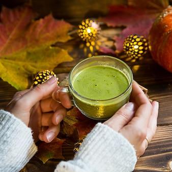 Zielona japońska herbata matcha z pianką w przezroczystej filiżance na drewnianym stole jesienią martwa natura. kobieca dłoń z długimi białymi, swetrowymi rękawami rozgrzewana jest napojem. skoncentruj się na pucharze. ciepła atmosfera i komfort