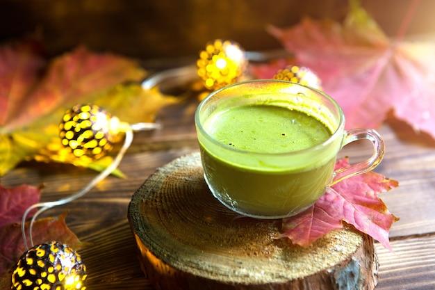 Zielona japońska herbata matcha z pianką w przezroczystej filiżance na drewnianym stole w jesień martwa natura. ciepła atmosfera i wygoda, girlandy świetlne, liście klonu czerwonego, laski cynamonu, dynia, ciasteczka, plasterek.