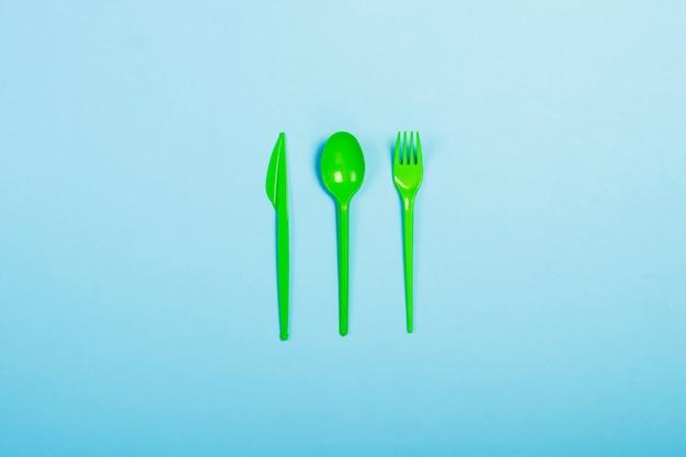 Zielona jednorazowa plastikowa zastawa stołowa i urządzenia do jedzenia na niebieskim tle. widelec, łyżka i nóż. koncepcja plastiku, szkodliwe, zanieczyszczenie środowiska, zatrzymaj plastik. leżał płasko, widok z góry.