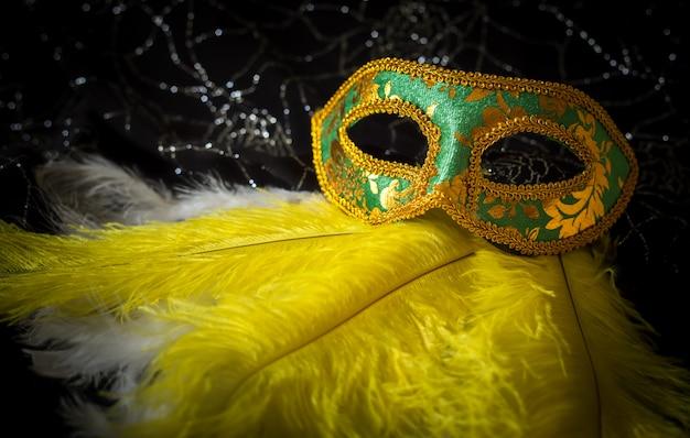 Zielona karnawałowa maska z żółtymi i białymi piórkami i błyszczącym tłem