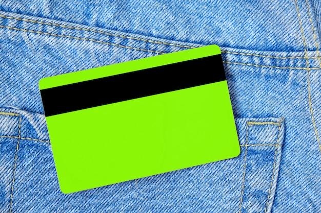 Zielona karta kredytowa w niebieskim poket z klasycznymi jeansami