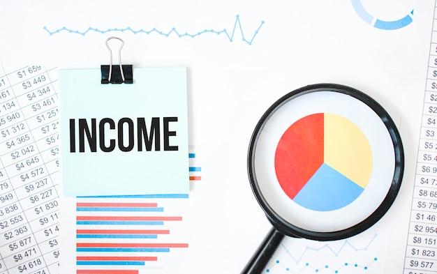Zielona karta na białym notatniku i lupa na dokumentacji finansowej. tekst dochodu. pomysł na biznes