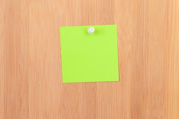 Zielona karteczka przypięta do drewnianej tablicy ogłoszeń wooden