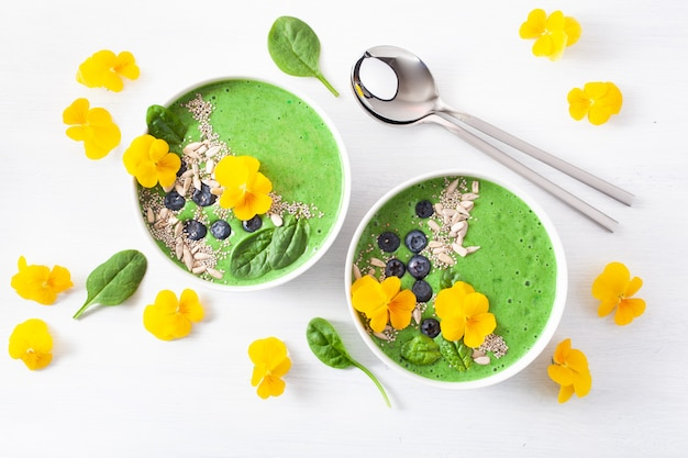 Zielona koktajlowa szpinakowa miska z jagodami, nasionami chia i jadalnymi kwiatami bratka