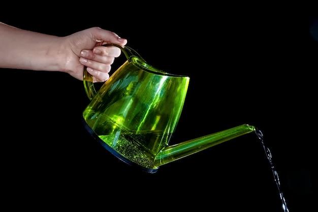 Zielona konewka w ręku na białym tle