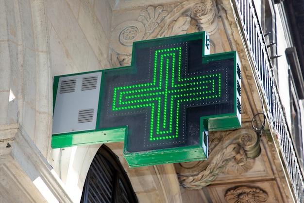 Zielona krzyż apteka podpisuje wewnątrz ulicznego budynku sklep