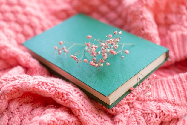 Zielona książka z suchymi kwiatami na różowym ciepłym swetrze z dzianiny