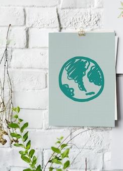 Zielona kula ziemska rysująca na papierowym plakacie na biel ścianie