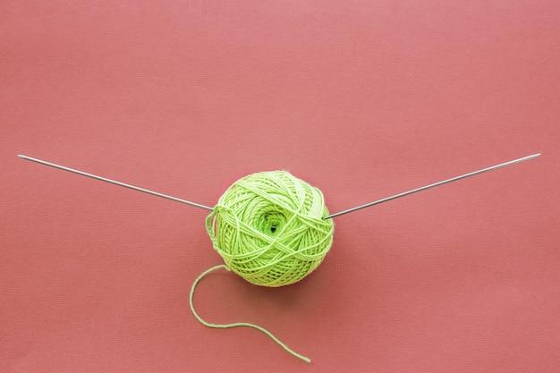 Zielona kulka przędzy dziewiarskiej i widok z góry igły na różowym tle