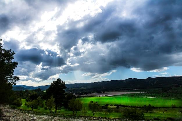 Zielona łąka w dzień z białymi i szarymi chmurami i promieniami słońca z górami w tle.
