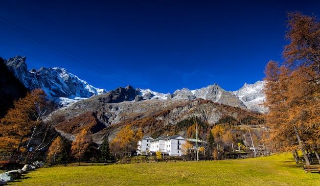 Zielona łąka z ogromnymi górami w małej wiosce w alpach