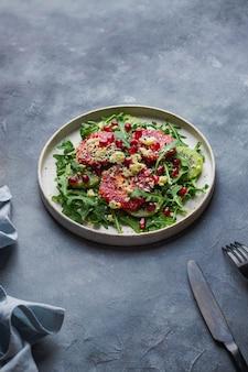 Zielona letnia sałatka podawana na niebieskim kamieniu z czarnym widelcem i nożem. koncepcja zdrowego odżywiania.