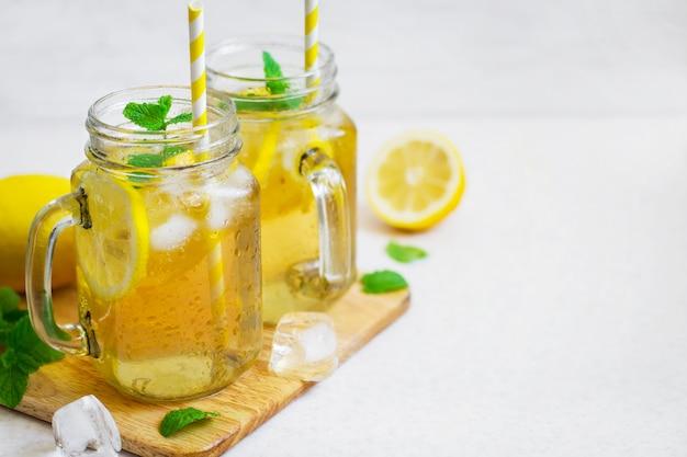 Zielona lodowa herbata z cytryną i mennicą w szklanym słoju.