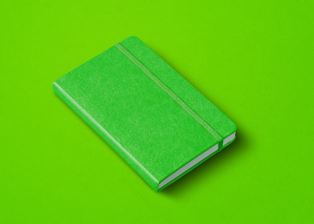 Zielona makieta zamkniętego notebooka na białym tle na kolorowym tle