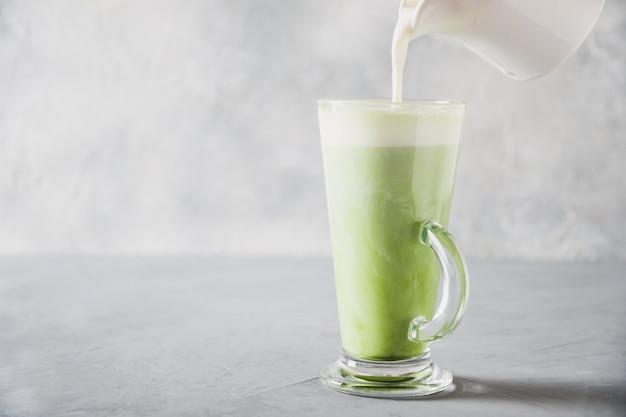 Zielona matcha herbata i mleko w latte szkle na popielatym stole.