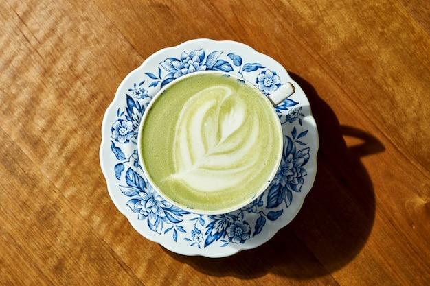 Zielona matcha w białym kubku na drewnianym tle. latte art na meczu