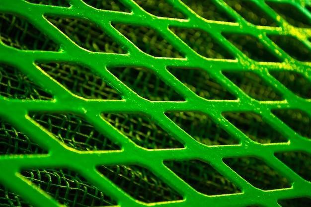 Zielona metalowa krata w kształcie rombu z bliska, pod cienką metalową siatką.