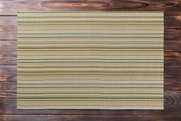 Zielona miejsce mata dla naczynia na drewnianym tle