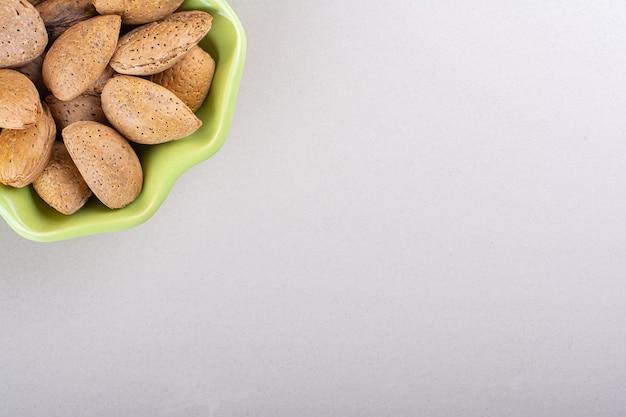 Zielona miska łuskanych migdałów organicznych na białym tle. zdjęcie wysokiej jakości