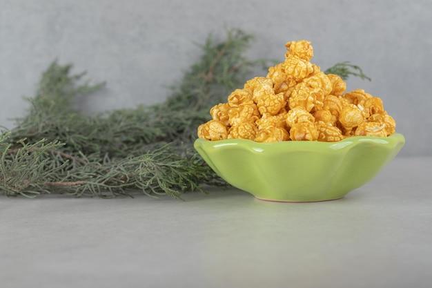 Zielona miska w kształcie kwiatka, wiecznie zielone liście i popcornowe cukierki na marmurowym stole.