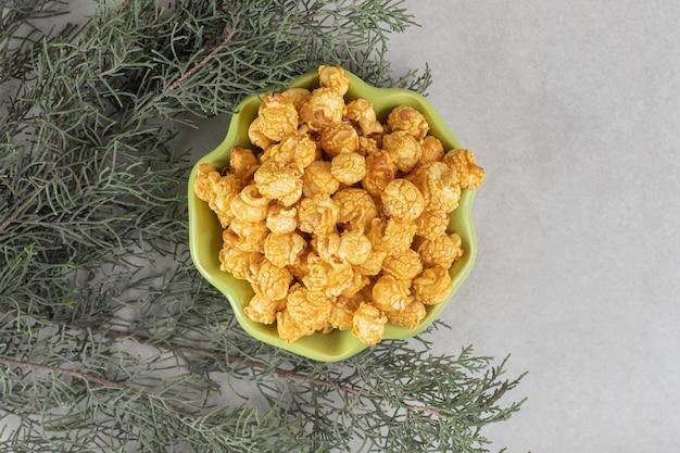 Zielona miska w kształcie kwiatu, pełna karmelowego popcornu, zagnieżdżona wśród gałęzi drzew na marmurowym stole.