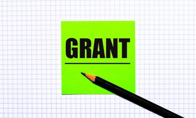 Zielona naklejka z napisem grant i czarnym ołówkiem na papierze w kratkę