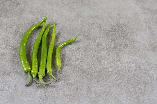 Zielona ostra papryka na marmurowym stole.