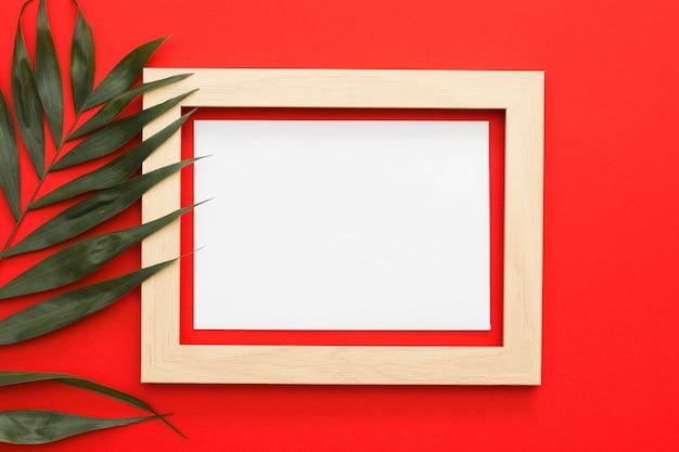 Zielona palma opuszcza gałąź z drewnianą ramą na czerwonym tle