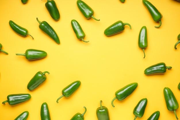 Zielona papryczka chili. grupa papryki jalapeno na żółtym tle, miejsce na tekst, widok z góry.