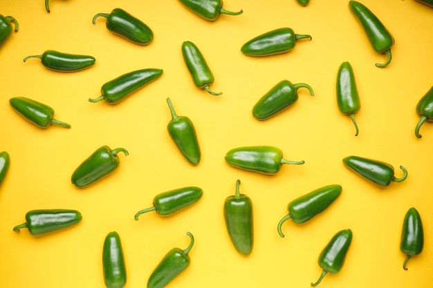 Zielona papryczka chili. grupa papryki jalapeno na żółtym tle, widok z góry.