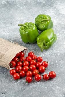 Zielona papryka z pomidorkami koktajlowymi w rustykalnej torbie na marmurowym stole.