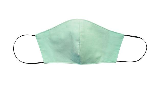 Zielona pastelowa sukienna twarzy maska odizolowywająca na białym tle z ścinek ścieżką. z powodu braku medycznych masek ochronnych podczas pandemii koronawirusa (covid-19), zdrowi ludzie zamiast tego noszą bawełniane maski.