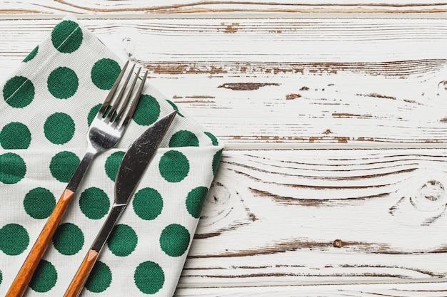 Zielona polki kropki pielucha na wietrzejącym drewnianym tle, kopii przestrzeń