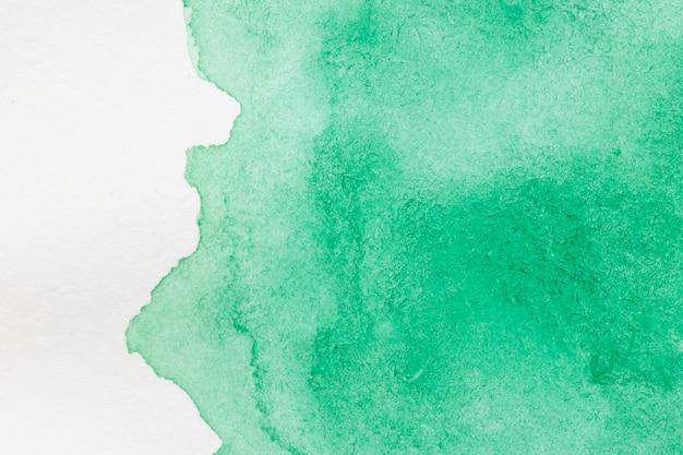 Zielona ręcznie malowana plama na białej powierzchni
