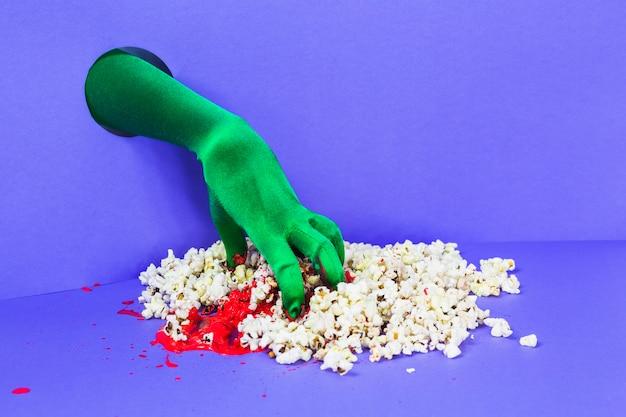 Zielona ręka z ścianą chwytając popcorn