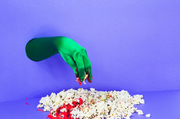 Zielona ręka zbierająca popcorn