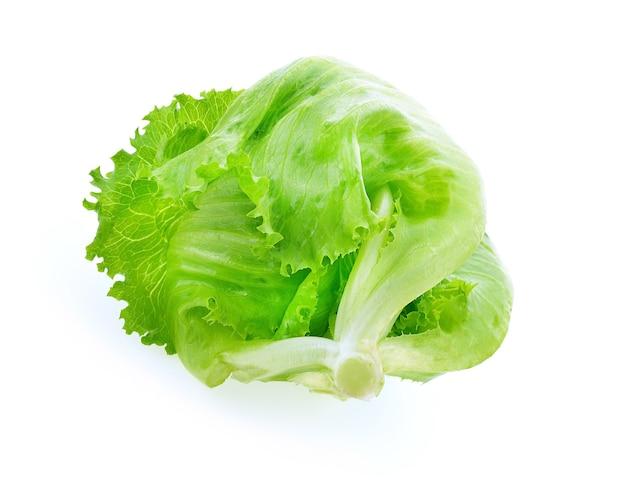 Zielona sałata lodowa na białej powierzchni. warzywo na sałatkę. zielona sałata lodowa o wysokiej zawartości witamin i błonnika.