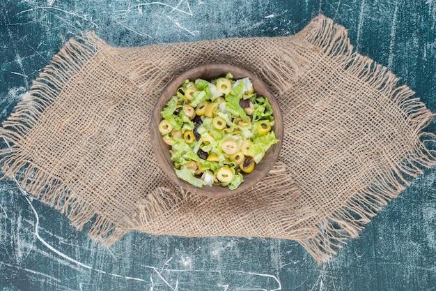 Zielona sałata z posiekaną sałatą na niebieskiej powierzchni.