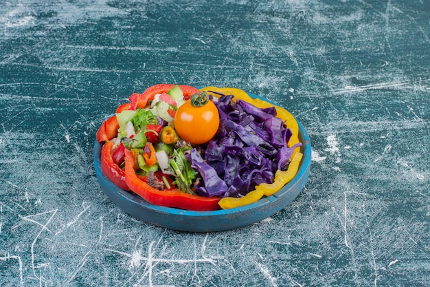 Zielona sałata z siekaną sałatą, fioletową kapustą, papryczką chili i pomidorami.
