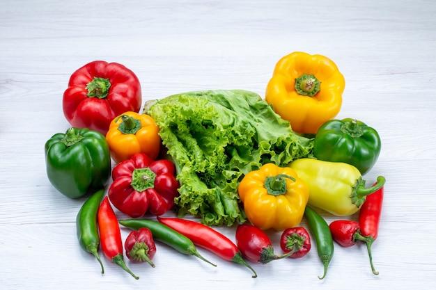 Zielona sałatka wraz z pełną papryką i ostrą papryką na lekkim biurku, składnik dań roślinnych