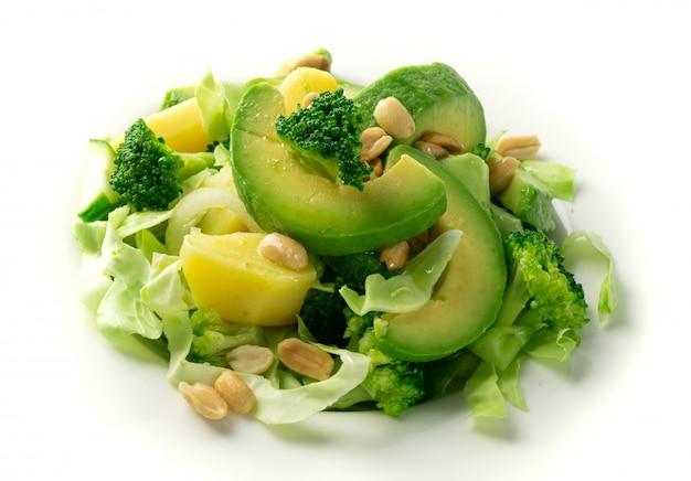 Zielona sałatka z awokado, ogórkiem i orzechami na białym talerzu