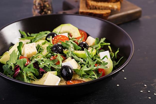Zielona sałatka z pokrojonym awokado, pomidorami koktajlowymi, czarnymi oliwkami i serem. zdrowa dieta wegetariańska letnia sałatka jarzynowa. ustawienie stołu koncepcja żywności.