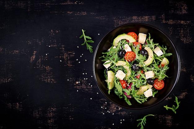 Zielona sałatka z pokrojonym awokado, pomidorami koktajlowymi, czarnymi oliwkami i serem.
