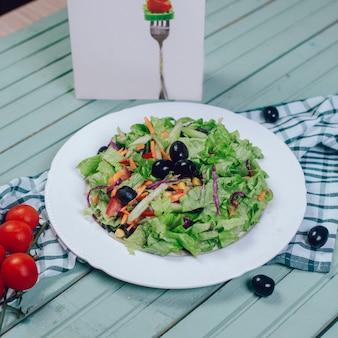 Zielona sałatka z posiekaną sałatą i czarnymi oliwkami