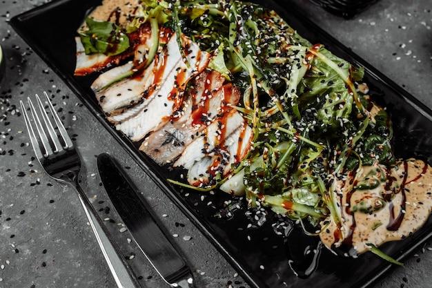 Zielona sałatka z wędzonymi pomarańczami z ryby węgorza i plastrami awokado na płasko leżała kuchnia japońska